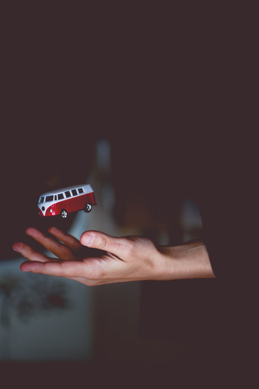 Picture of a toy bus being tossed by a hand